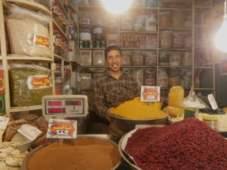 A smiling spice seller in Isfahan's grand bazaar.